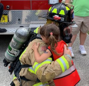 Little Girl hugging Flagler Fire Fighter Friendly at Ity Bity School Readiness 2019