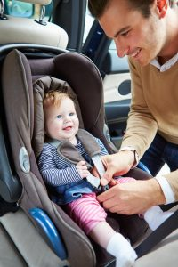 Father is buckling baby into a rear-facing car seat